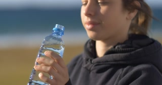 drinking fresh water from a recycled plastic water bottle young adult