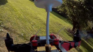 Drone racing quad copter flying FPV through trees in park