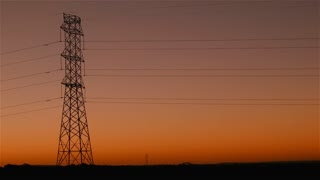 Energy Transmission Power Line Tower Pylon Structures at Sunset: Overhead power line is a structure used in electric power transmission and distribution to transmit electrical energy electricity along large distances.
