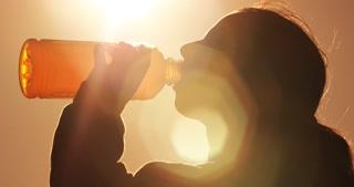 fitness girl drinking sports drink from plastic bottle outside in park