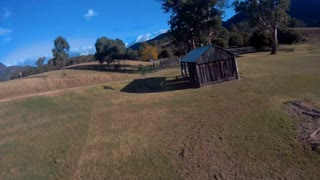 FPV drone quad copter flying fast on farm aerial footage