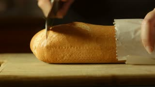 fresh golden brown bread cutting up in kitchen on bread board
