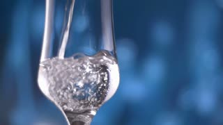 Fresh natural cool water pour into glass slow motion with bubbles