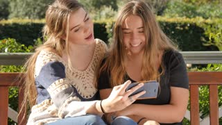Gen Z bff teenage girls with mobile smartphone technology taking funny selfie
