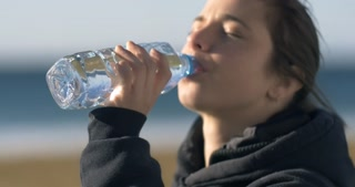 Girl drinking fresh natural water from a plastic bottle