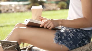 Girl student sitting under a tree reading a book driking coffee