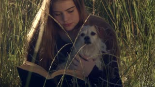 girl with pet dog reading book relaxing outdoors in sunshine.This beautiful young teenage girl with her pet dog is reading a book outdoors in the sun and long grass relaxing in a happy content cheerful manner enjoying life.