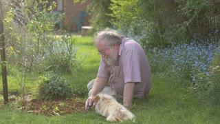 Grandfather retired elderly mature senior adult retirement gardening with dog