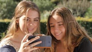 Happy teenage girls selfie shot mobile phone pulling funny faces expression