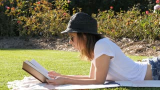 Hipster young woman uni student relaxing reading a book with hat and sunglasses