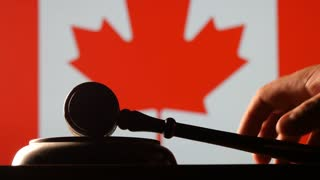 Judge calling order with hammer and gavel in canadian court with flag background