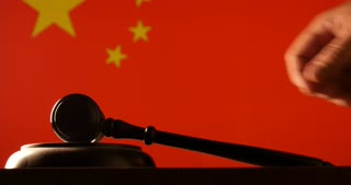 Judge calling order with hammer and gavel in china court with flag background