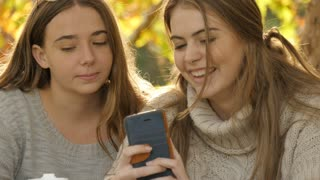 Looking at mobile cell phone technology two teen girls laughing autumn fall