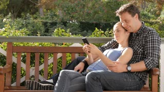 Millennial couple cuddling looking at smart phone device social media