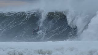 NSW, AUSTRALIA - JUNE 20 Bodyboarder surfing massive waves of coast during storm