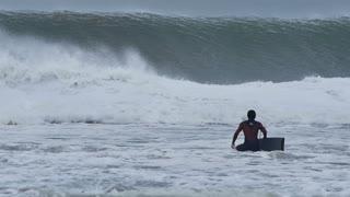 NSW, AUSTRALIA - JUNE 2016: bodyboarder surfer big stormy sea waves from cyclone