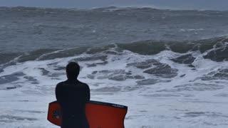 NSW, AUSTRALIA - JUNE 2016: bodyboarder surfer looking at stormy sea waves