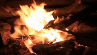 outdoor camping campfire at night with buring wood on fire