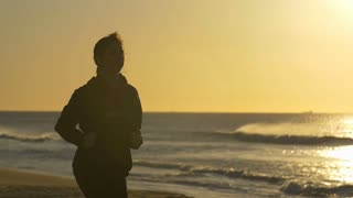 Person jogging exercising by beach with sun behind slowmo
