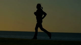 Person jogging exercising in park with sun behind slowmo
