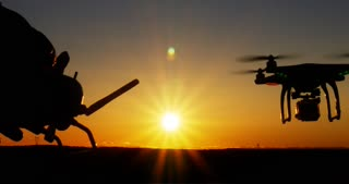 Person operating drone quadcopter aircraft via remote control at sunset