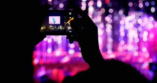 Person taking video and photos at concert stage event