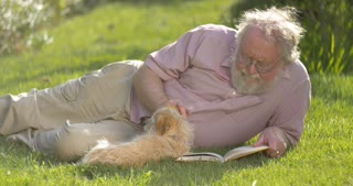 Portrait of retired elderly man relaxing outdoors reading a book with dog