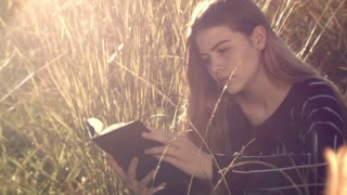 Reading book young teenage girl sitting in grass relaxing outdoors in sun This beautiful young teenage girl is reading a book outdoors in the sun and long grass relaxing in a happy content cheerful manner enjoying life.