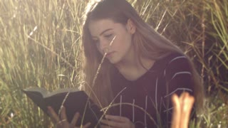 Reading book young teenage girl sitting in grass relaxing outdoors in sun