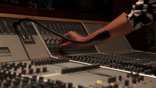 Recording studio music mixing desk console with engineer hand turning nob