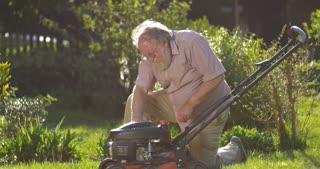 Retired elderly man mowing lawn enjoying retirement