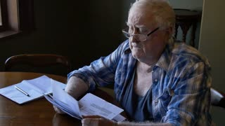 Retired pensioner at table stressed looking at debt