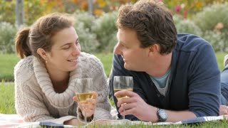 Romantic young couple in park drink wine celebrating marriage engagement