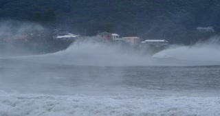 Sea spray form massive waves that are braking along coastal town