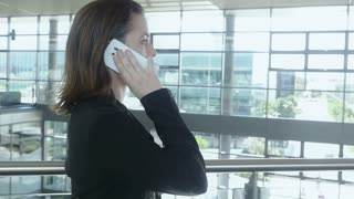 Slow motion businesswoman walking in office building talking on phone