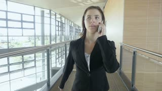 Slow motion businesswoman walking in office building talking on phone