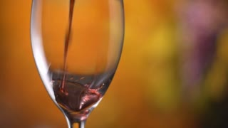 Slowmotion clip of red wine being poured into a wine glass. This red merlot, pinot, cabernet wine clip could be used by winerys, vineyeard or for wine tasing to highlight celebration and luxury.
