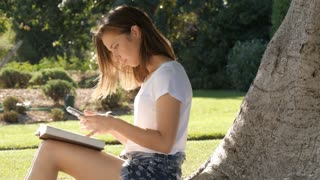 Student using mobile smartphone technology to study and learn outdoors in park