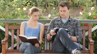 Student woman tutors man in study research taking written notes on campus