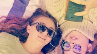 Stylish hip teenage girls with sunglasses listening to music sharing headphones