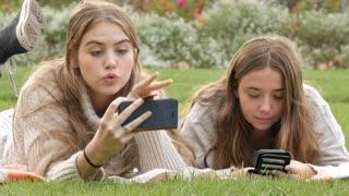 Teenage girls enjoying taking selfie and texting on mobile smart phone