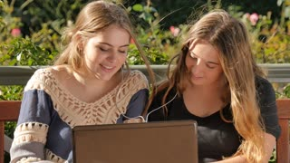 Teenage girls using laptop to chat with friends social media listening to music