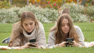 Texting social media teenage girls checking likes and messages mobile phone
