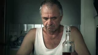 This Alcoholic male man sitting at table with a bottle of alcohol liquor beverage suffering effects of alcoholism and associated drug addiction disorders such as, desperation, stress, sadness, loneliness, anger and depression.