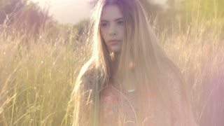 This portrait footage is of a beautiful young girl fashion model walking in long grass at sunset with a neutral sexy seductive look. This would suit fashion and advertising.