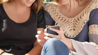 Two bff girl friends sitting on a bench looking a mobile smart phone laughing