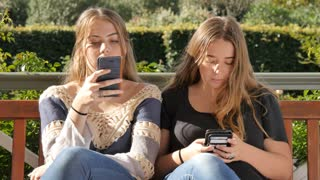 Two bored teenage girl friends texting on social media Internet technology