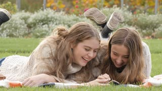 Two happy young teenage girls relaxing laughing at photos on mobile phone