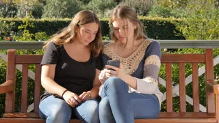 Two teenage girls sitting in park looking at social media on smartphone laughing