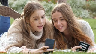 Two young woman funny expression faces at mobile phone camera technology